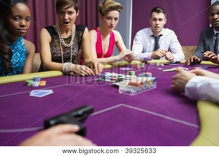 People looking scared at gun on poker table in casino