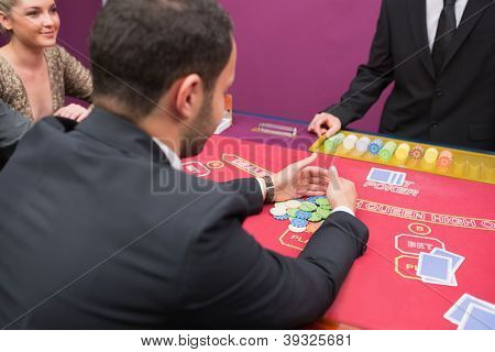 Man taking his prize at poker in the casino
