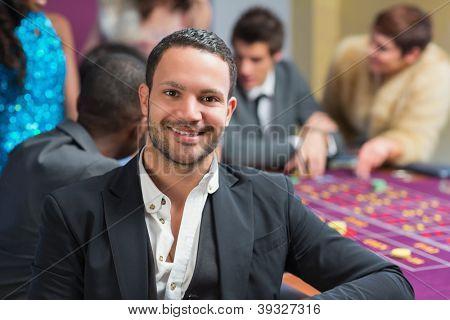 Lächelnder Mann sitzend, stützte sich auf Roulette-Tisch im Casino
