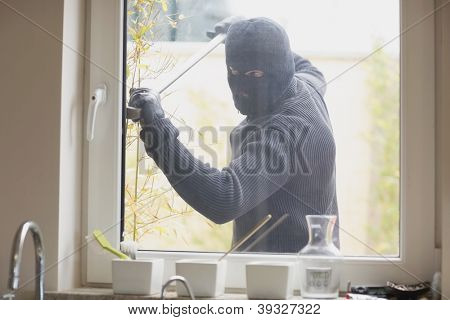 Burglar breaking a kitchen window with a crobar from outside