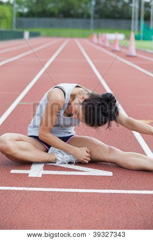 Woman stretching her leg on a track