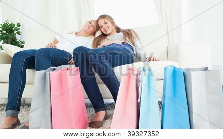 A smiling girl and her friend as she looks at the camera with bags of shopping