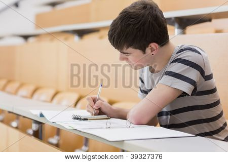 Student sitting at the lecture hall while writing on notepad