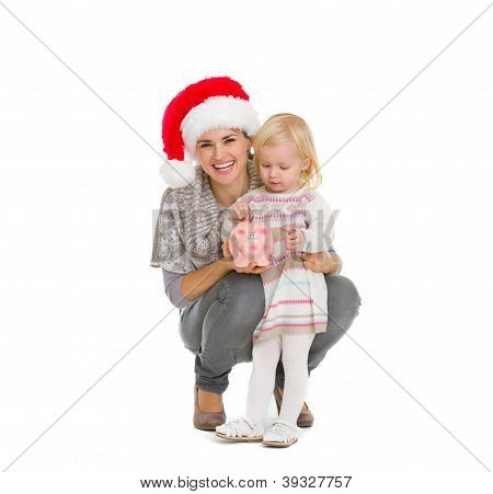 Happy Mother In Christmas Hat And Baby Girl Putting Coin Into Pi