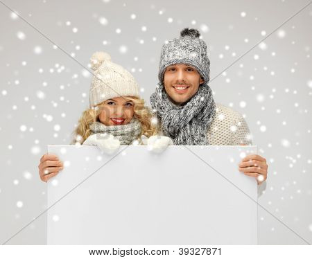 picture of family couple in a winter clothes holding blank board