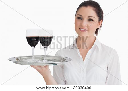 Smiling woman holding silver tray with glasses of red wine