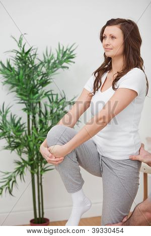 Woman standing while stretching her leg in a room
