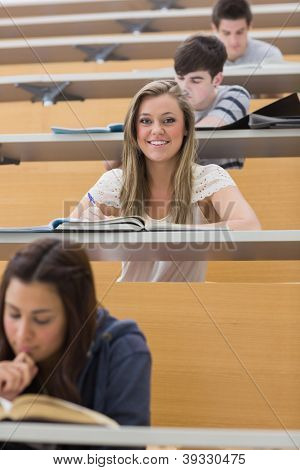 Student sitting at the lecture hall smiling and taking notes