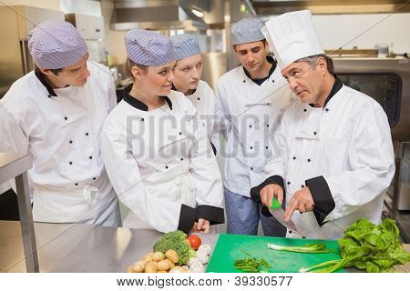 Trainees learning vegetable slicing in the kitchen