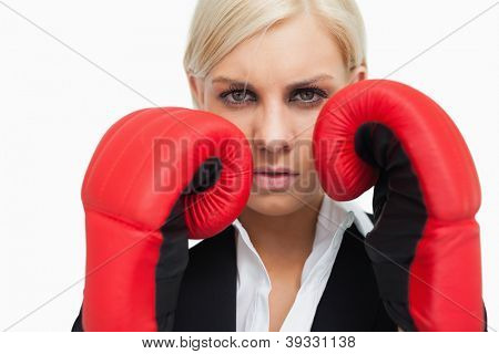 Serious blonde woman with red gloves fighting against white background