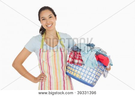Happy woman in apron holding full laundry basket