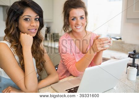Two happy friends with laptop having coffee in kitchen