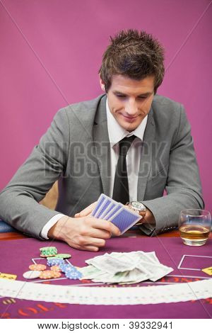 Smiling man sitting at table in a casino while playing poker and holding cards