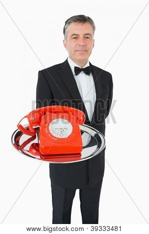 Well-dressed waiter holding a red phone on a silver tray on white background