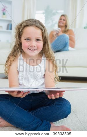 Laughing daughter with a book while her mother is resting on the sofa