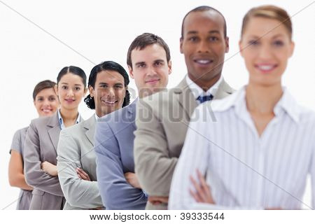 Close-up of workmates dressed in suits crossing their arms in a single line with focus on the last two people