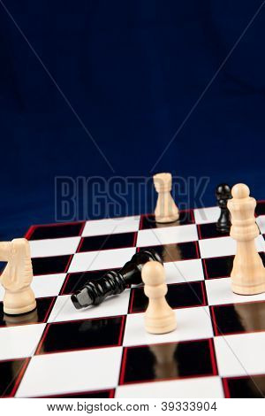 Black queen lying at the chessboard while white chessmen surrounding it