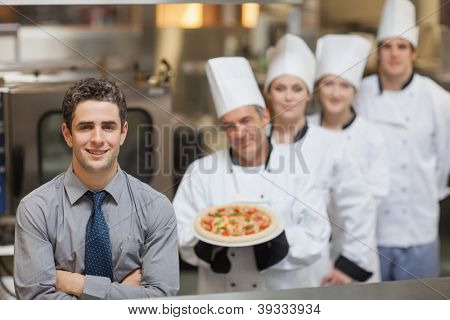 Waiter standing in front of Chef's holding a pizza