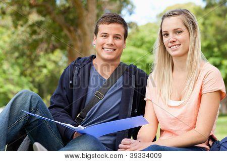 Retrato de un tutor de ayudar a un adolescente a revisar en un parque