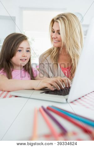 Little girl typing on laptop with mother smiling in the kitchen