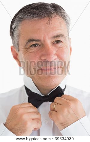 Happy man adjusting his bow tie in fornt of camera