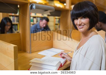 Black-haired woman reading a book in library at desk