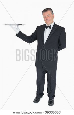 Smiling waiter holding empty silver tray