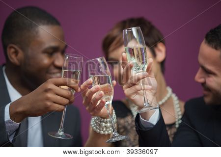 Three people toasting and celebrating in a casino while sitting at table