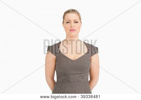 Woman standing with her arms behind her back against white background