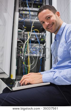 Smiling man using the laptop next to servers in data center