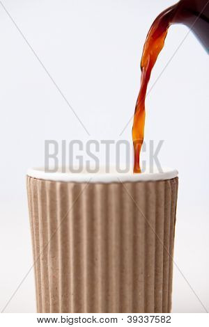 Paper cup being filled with coffee against a white background