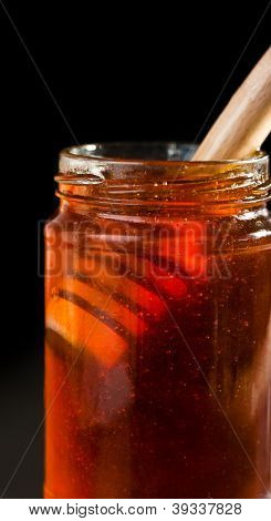 Close up of a honey jar with a honey dipper against a black bakground