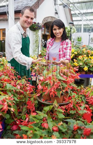 Smiling customer touching plant with employee in garden center