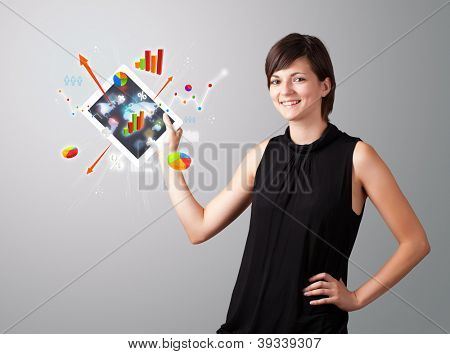 Beautiful woman holding modern tablet with colorful diagrams and graphs