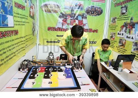 SUBANG JAYA - NOV 10: Unidentified students from Malaysia shows an intelligent robot that could identify and solve a number-puzzle at the World Robot Olympaid on Nov 10, 2012 in Subang Jaya, Malaysia.