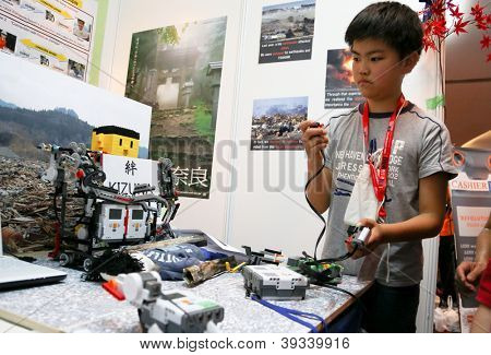 SUBANG JAYA - NOVEMBER 10: An unidentified students from Japan tests his remote control robot made to access dangerous areas at the World Robot Olympaid on November 10, 2012 in Subang Jaya, Malaysia.