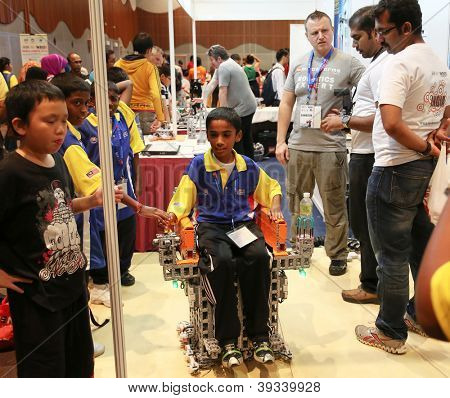 SUBANG JAYA - NOVEMBER 10: An unidentified student tests a wheel-chair robot at the World Robot Olympaid on November 10, 2012 in Subang Jaya, Malaysia. This year's theme is Robots connecting people.