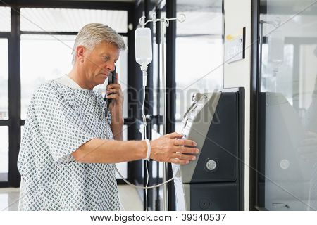 Man with I.V drip using pay phone in hospital corridor