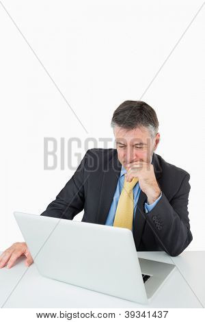 Thoughtful businessman sitting at his desk with a laptop on a white background
