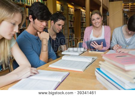 Woman holding a tablet pc while sitting at table of studying students in college library