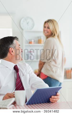 Couple smiling at each other at the kitchen while man is sitting holding a tablet pc and coffee beofre work