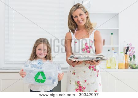 Smiling mother and daughter holding recycling waster