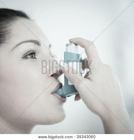 Woman using an asthma inhaler as prevention