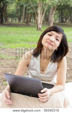 Asian Woman Flagging With Laptop Sitting At Park