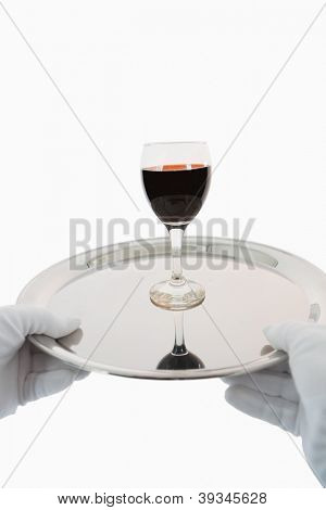 Waiter holding a glass of red wine on a silver tray