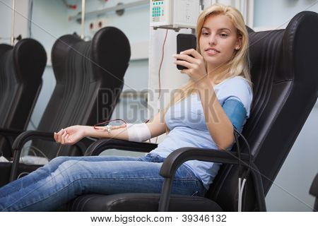 Mujer rubia relajante en una silla mientras se obtiene n hospital de diálisis