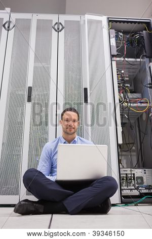 Man sitting in front of servers with his laptop on the floor of data center