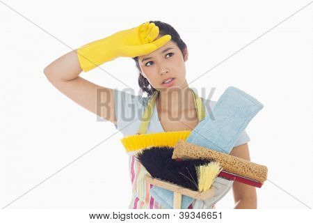 Weary woman holding brushes and mops and wiping her brow