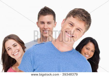 Ein lächelnd mann mit seinem Kopf geneigt, als seine Freunde stehen hinter ihm das gleiche in verschiedenen direc