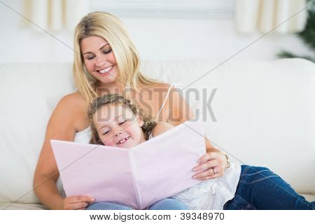 Daughter and mother resting on the sofa reading a book